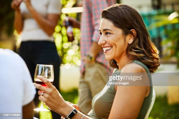 smiling young woman holding wineglass at party - medium length hair stock pictures, royalty-free photos & images