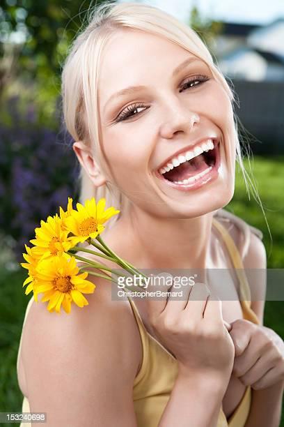 Sorridente giovane donna con daisies giallo