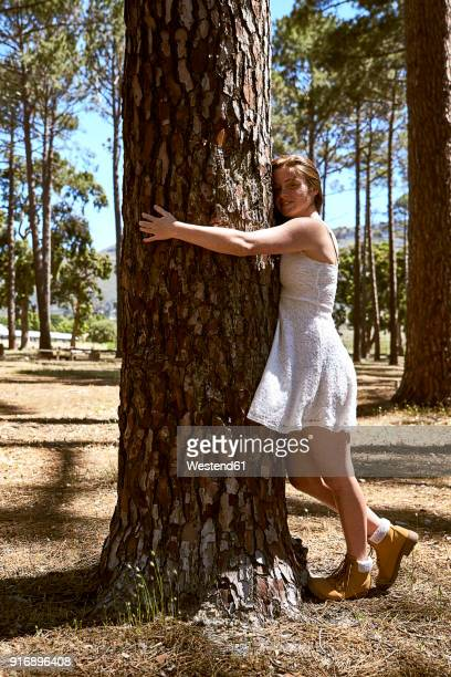 smiling young woman hugging a tree in forest - tree hugging stock pictures, royalty-free photos & images