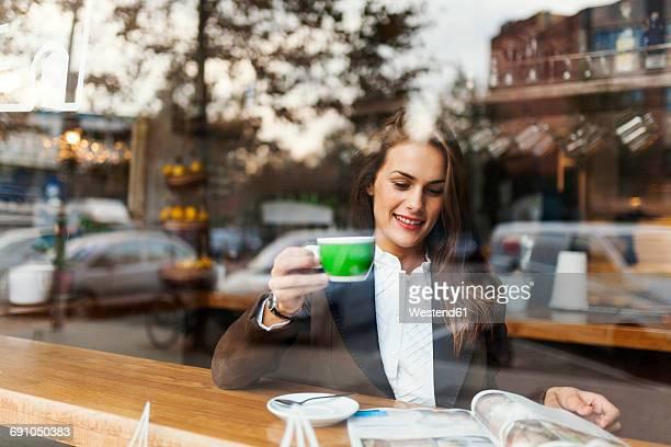 smiling young woman in a cafe reading a magazine - treats magazine fotografías e imágenes de stock