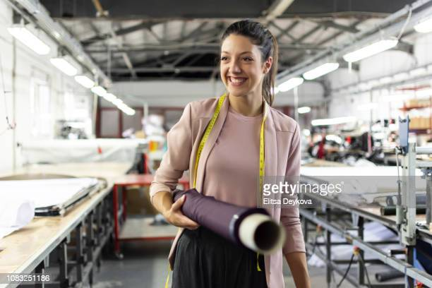 smiling young woman in a fashion factory - textile stock pictures, royalty-free photos & images