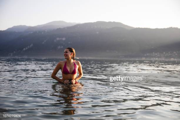 smiling young woman in a lake - chum stock-fotos und bilder