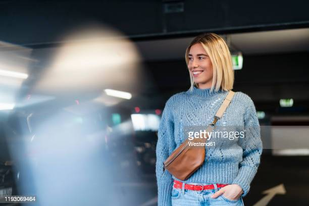 smiling young woman in a parking garage - crossbody bag stock pictures, royalty-free photos & images