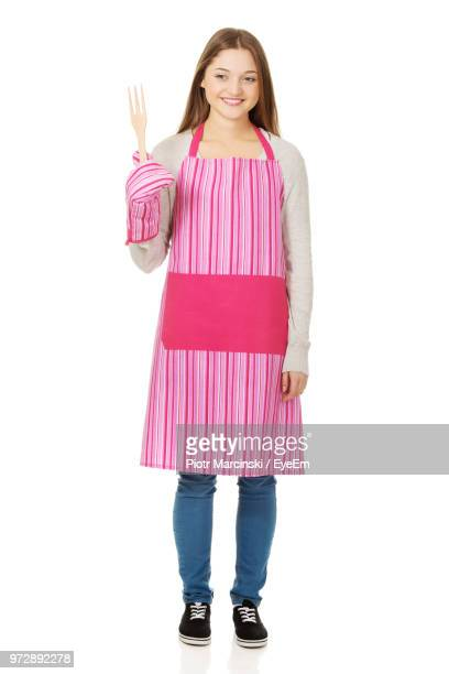 Smiling Young Woman In Apron Standing Against White Background