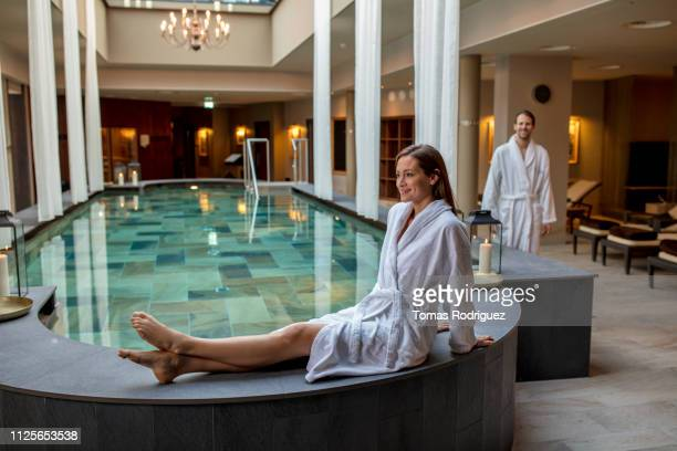 smiling young woman in bathrobe sitting at the poolside in a spa with man in background - health farm stock pictures, royalty-free photos & images