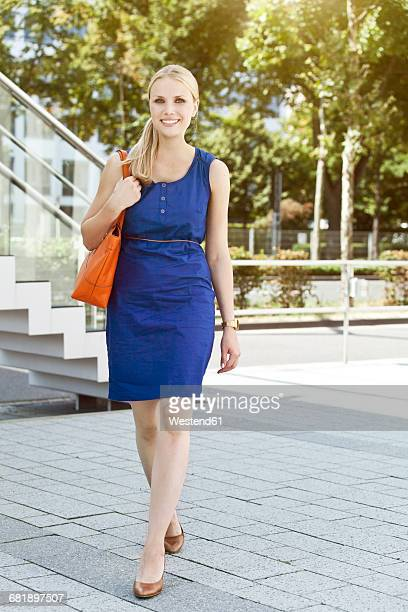 Smiling young woman in blue dress on the go