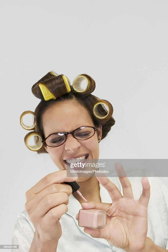 Smiling young woman in curlers polishing her fingernails : Stock Photo