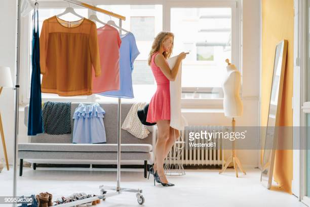 smiling young woman in fashion studio looking in mirror - dressmaker's model stock photos and pictures