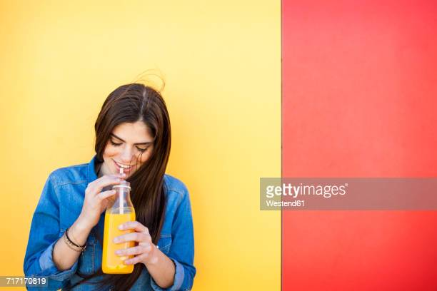 Smiling young woman in front of colourful wall drinking orange juice