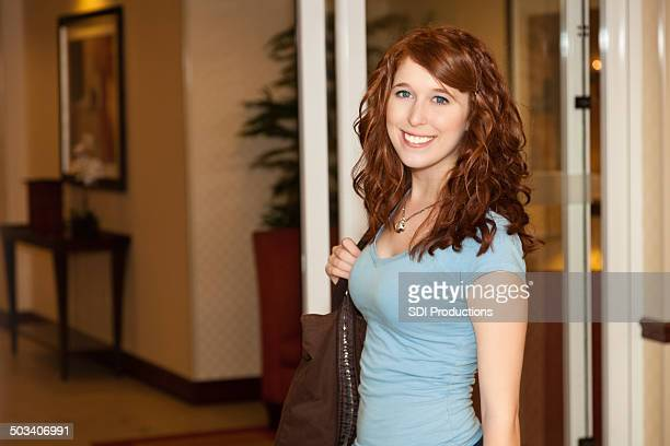 Smiling young woman in front of hotel entrance