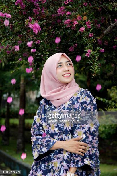 Smiling Young Woman In Hijab Standing Against Plants