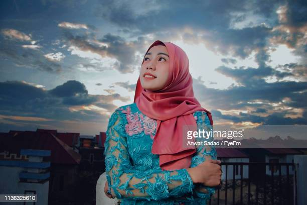 Smiling Young Woman In Hijab Standing Against Sky During Sunset