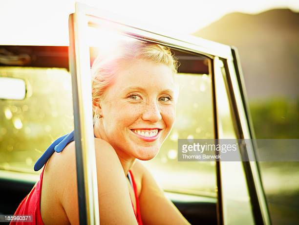 Smiling young woman in off road vehicle at sunset