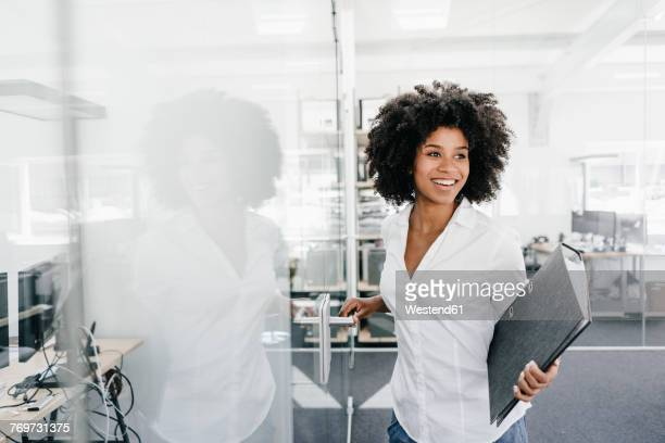 Smiling young woman in office holding file folder