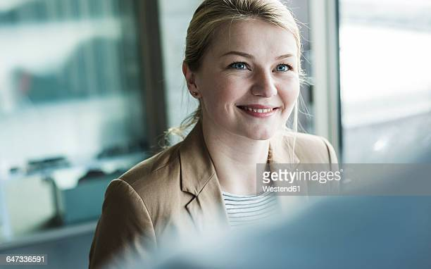 Smiling young woman in office looking at colleague