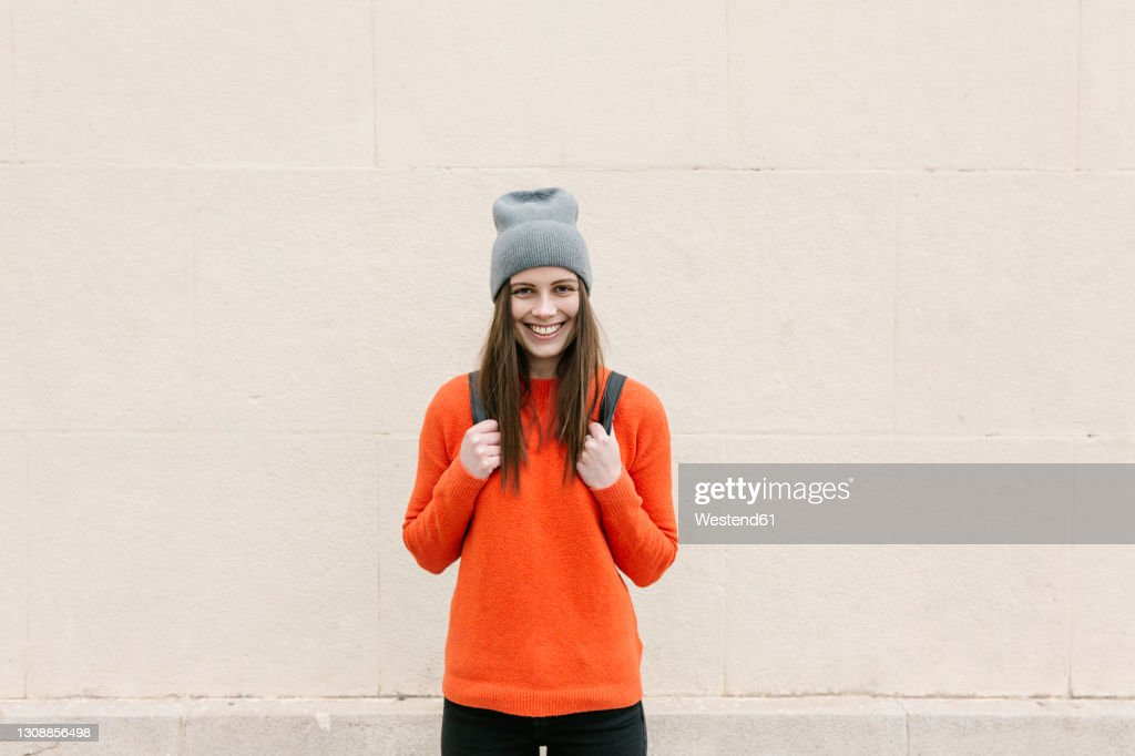 Smiling young woman in orange sweater standing against wall : ストックフォト
