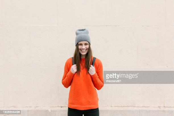 smiling young woman in orange sweater standing against wall - オレンジ色のシャツ ストックフォトと画像