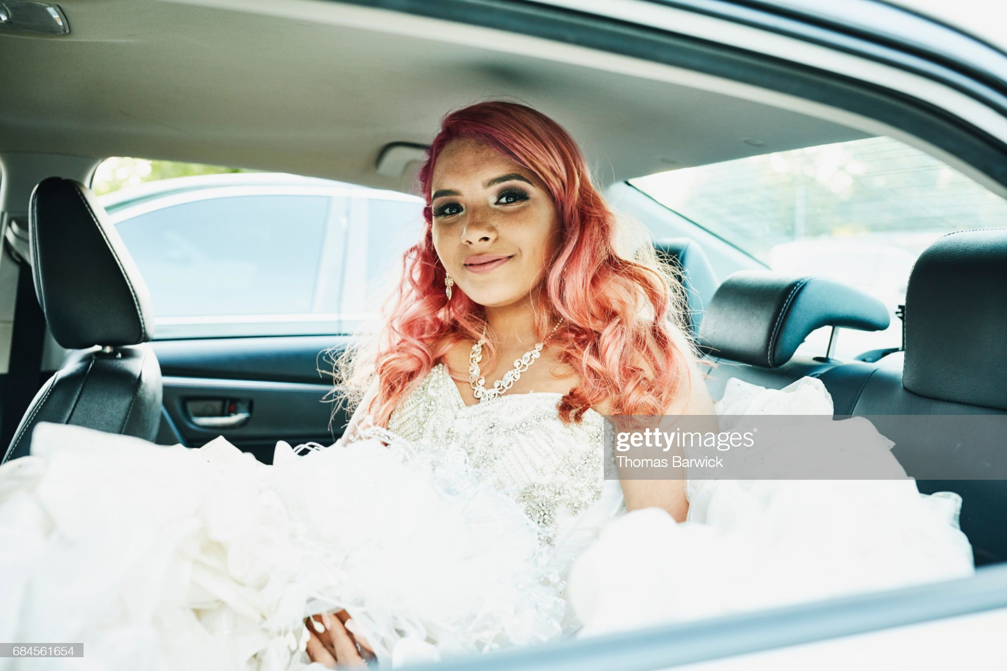 Smiling young woman in quinceanera gown sitting in back seat of car : Stock Photo