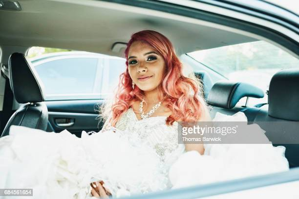 smiling young woman in quinceanera gown sitting in back seat of car - quinceanera stock pictures, royalty-free photos & images