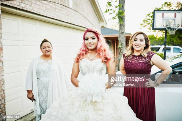 Smiling young woman in quinceanera gown standing in front of home with grandmother and aunt