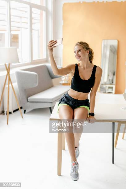 smiling young woman in sportswear taking a selfie - スポーツウェア ストックフォトと画像