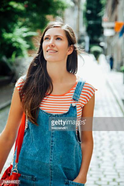 Smiling young woman in the city looking around