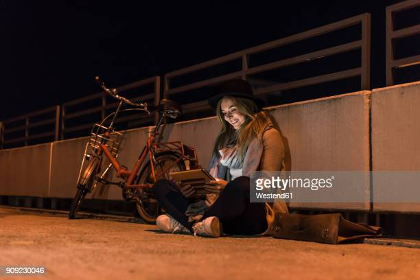 Smiling young woman in the city using tablet at night