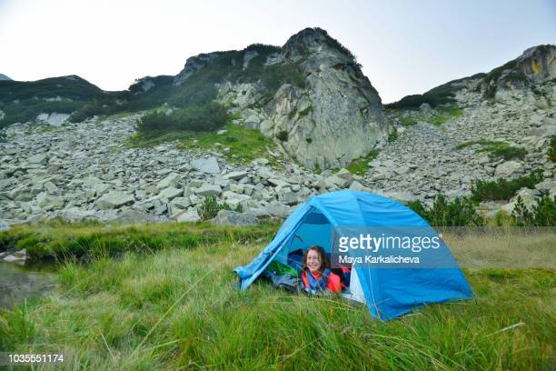 smiling young woman inside a tent, camping in a mountain valley - pirin mountains stock pictures, royalty-free photos & images