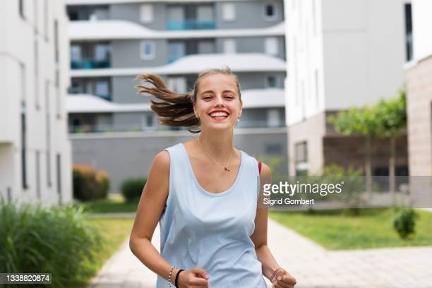 smiling young woman jogging - sigrid gombert stock pictures, royalty-free photos & images