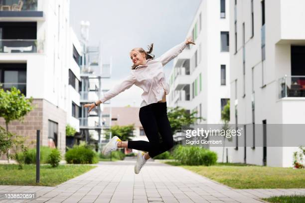 smiling young woman jumping in modern neighborhood - sigrid gombert stock pictures, royalty-free photos & images