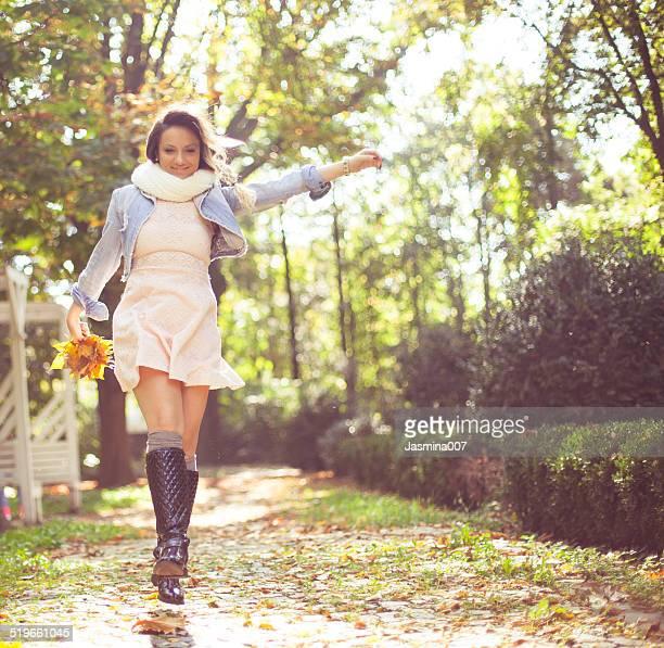 Souriante jeune femme sauter dans le parc