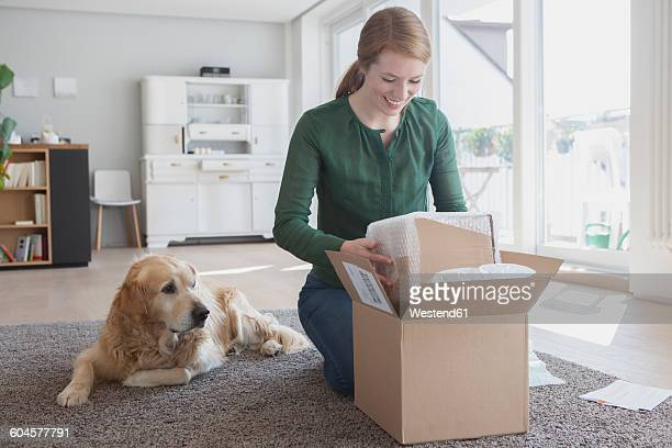 Smiling young woman kneeling on the floor beside her dog unpacking a parcel