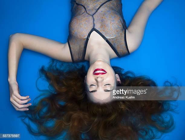 smiling young woman laying in water. - flotter sur l'eau photos et images de collection
