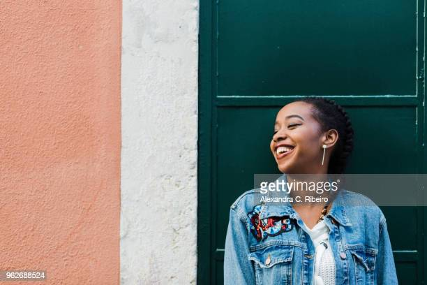 smiling young woman leaning against building - denim jacket stock pictures, royalty-free photos & images
