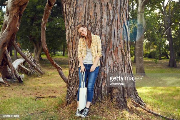 Smiling young woman leaning against tree trunk