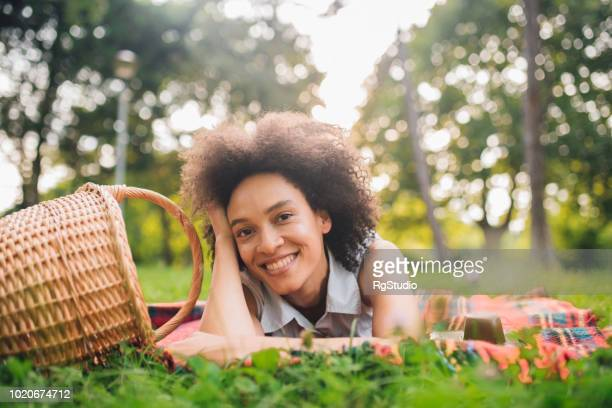 Smiling young woman leaning head on her hand while lying down on a picnic blanket