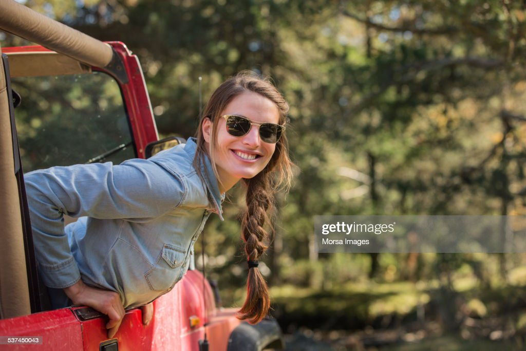 Smiling young woman leaning out of jeep : Stock Photo