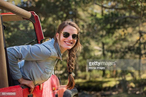 Smiling young woman leaning out of jeep