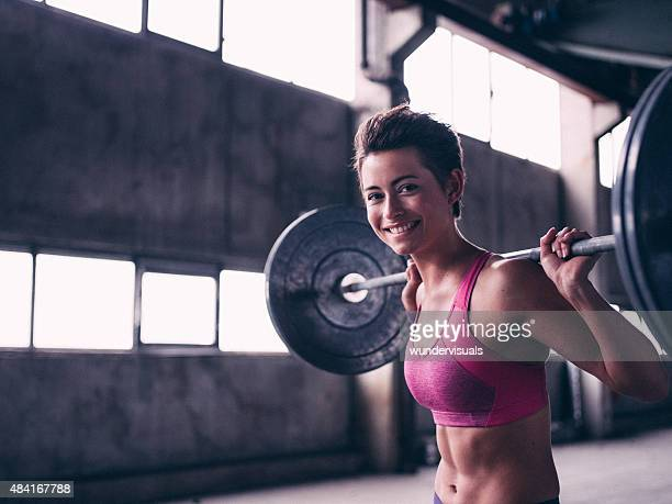 Smiling young woman lifting a barbell in a grungy setting