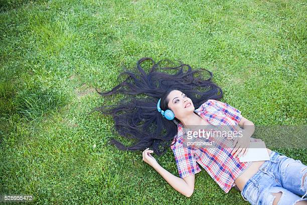 Smiling young woman listening music lying on ground