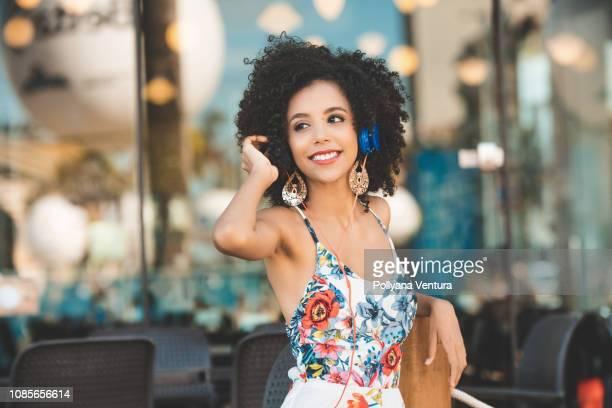 lächelnde junge frau musik über kopfhörer hören - brasilianischer abstammung stock-fotos und bilder