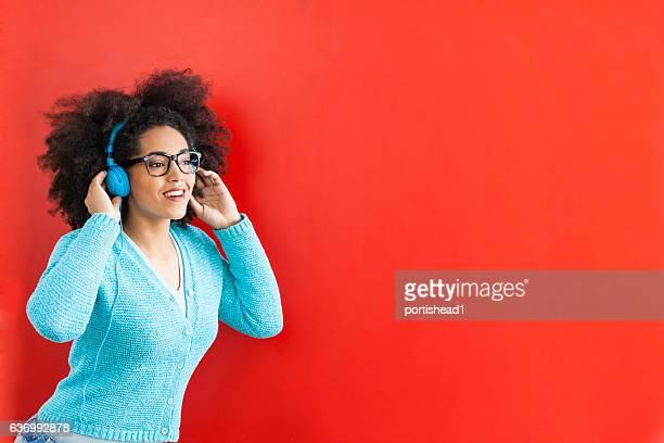 Jeune femme souriante en écoutant de la musique sur fond rouge