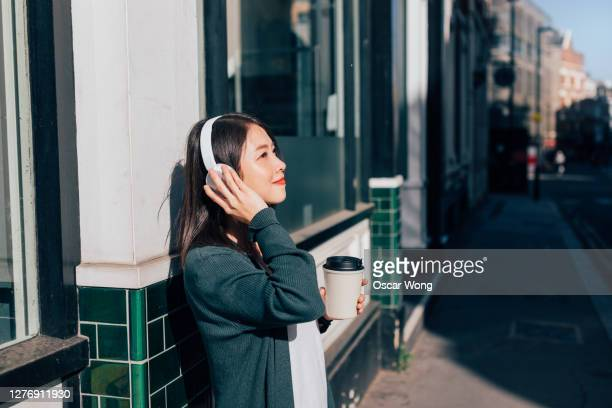 smiling young woman listening to music with bluetooth headphones outdoors - listening stock pictures, royalty-free photos & images