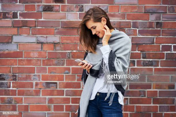 smiling young woman looking at cell phone in front of brick wall - shawl stock pictures, royalty-free photos & images