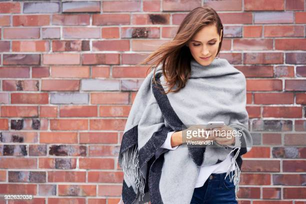 Smiling young woman looking at cell phone in front of brick wall