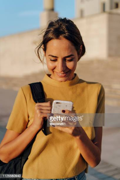 smiling young woman looking at cell phone outdoors - europa occidentale foto e immagini stock