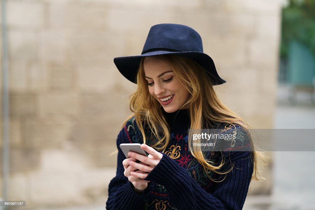 Smiling young woman looking at cell phone : Stock Photo