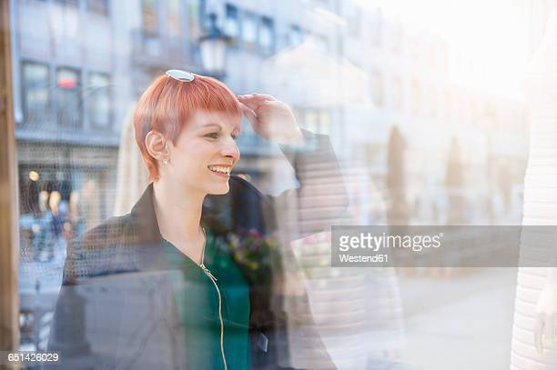 Smiling young woman looking at shop window