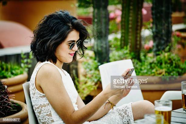 Smiling young woman looking at smartphone