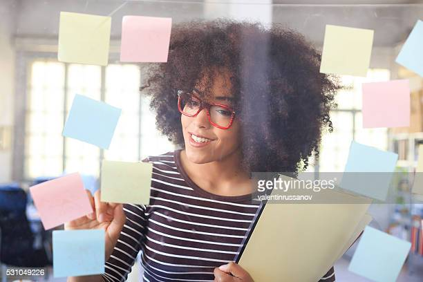 Smiling young woman looking at window with sticky notes